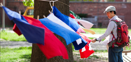 A Student examines flags on the University Yard.